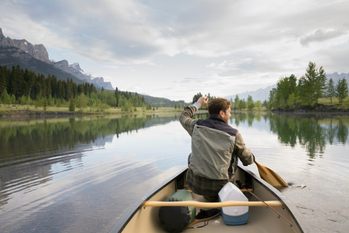 Man rowing canoe in still lake